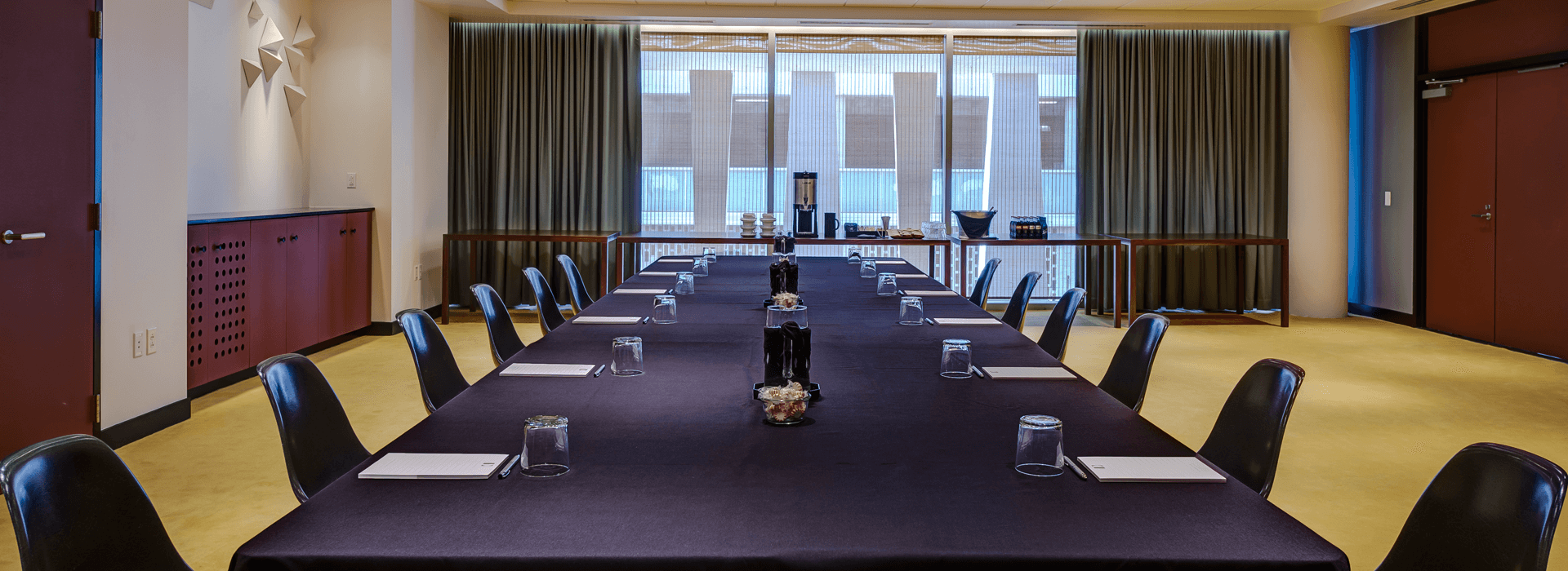 Meeting room table with chairs, with a window view at the end.