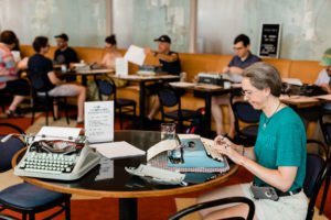 People typing on typewriters at The Durham Hotel