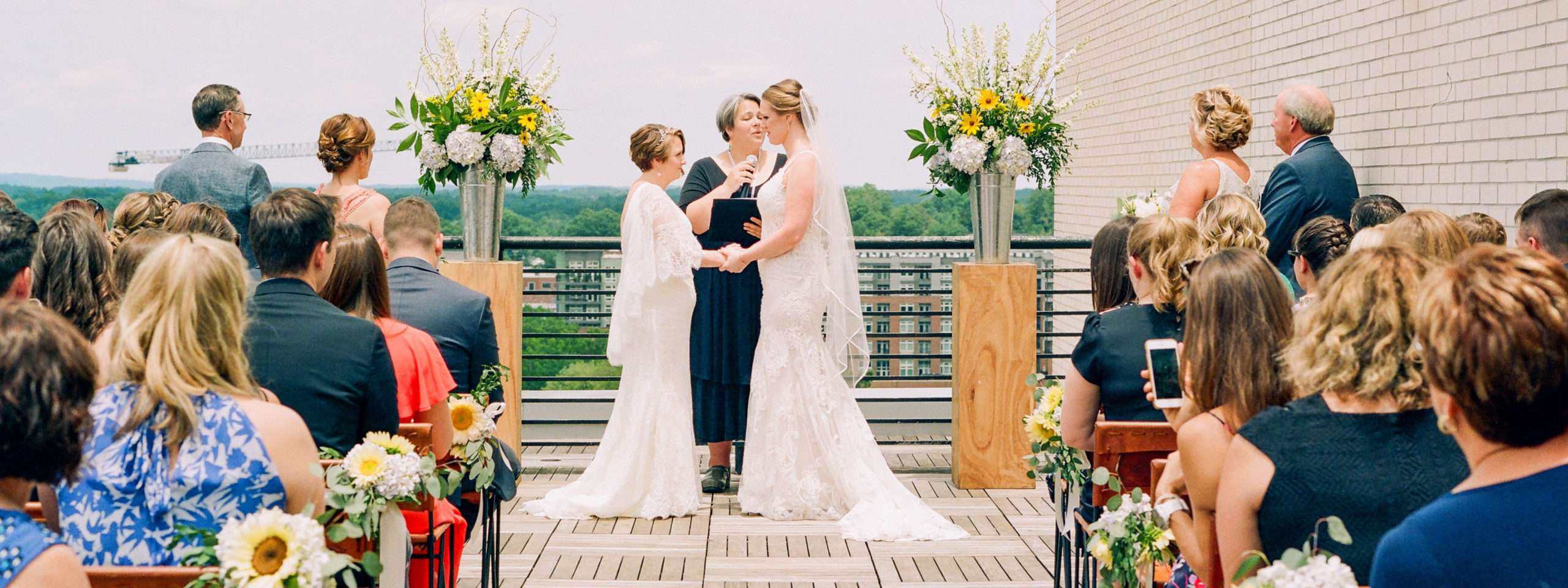 Two brides on the rooftop at The Durham Hotel exchanging wedding vows with friends & family